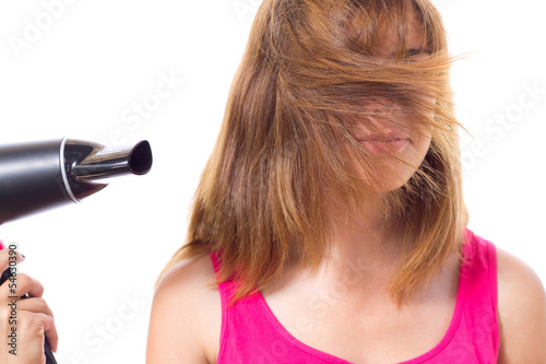 girl dries hair with electrical appliance