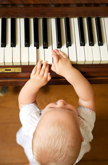 Portrait of a cute baby playing piano
