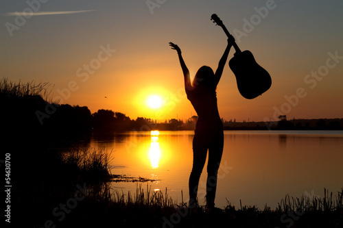 silhouette of a happy girl with a guitar by the river