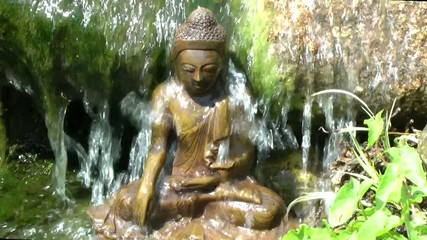 Buddha seated under a waterfall