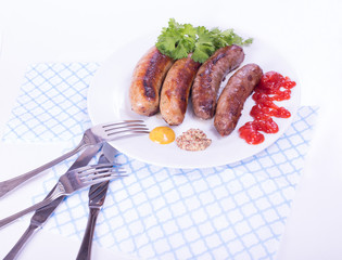 sausages on a plate with condiments