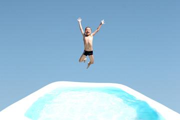Junge springt in den Pool