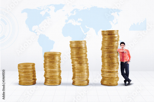 Businessman and gold coins growth on world map