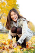 Autumn woman playing with colorful fall leaves