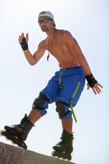 junger erwachsener mann im sommer mit rollerblades inlineskates