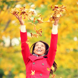 Autumn / fall woman happy throwing leaves