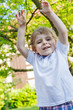 Portrait of smiling happy little boy in garden
