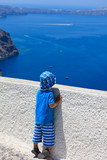little boy looking at Santorini, Greece