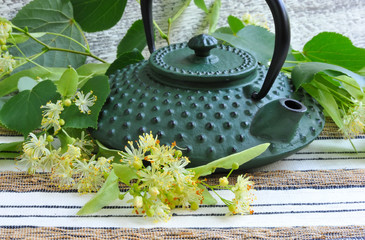Teapot with linden tea and flowers