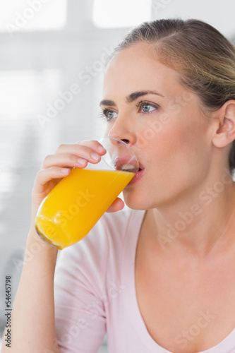 Thoughtful woman drinking orange juice