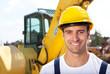 Freundlicher Bauarbeiter mit seinem Bagger