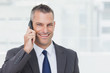 Cheerful businessman looking at camera while having a phone call