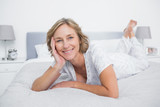 Content blonde woman lying on bed