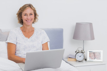 Happy blonde woman sitting in bed using laptop