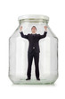 Young businessman in glass jar