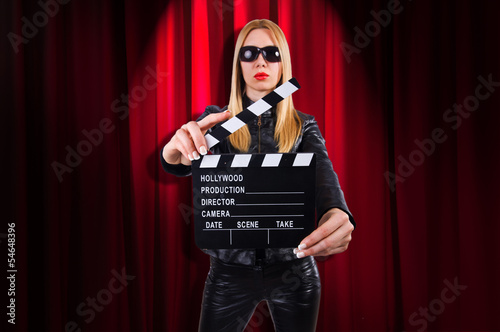 Girl with movie board against curtains