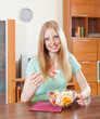 Positive long-haired woman eating  fruit salad