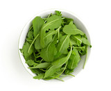 rucola in a glass bowl isolated on white background