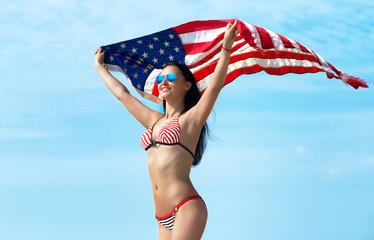 Smiling woman in bikini with American flag, blue sky