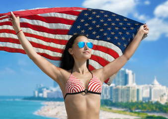 Happy girl in bikini with American flag fluttering in her hands