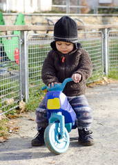 A little child playing at a playground with a  toy motorbike .