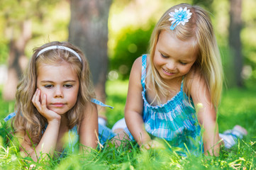 Two little sisters having fun in summer park