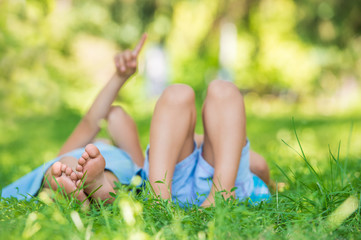 Group of happy children lying on green grass