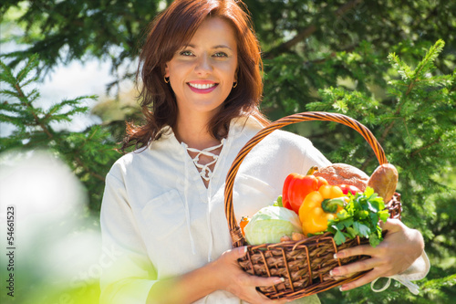 Woman holding basket of vegetables
