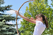 Teenage girl taking aim with a bow and arrow