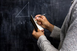 Man taking notes of math theorem on blackboard