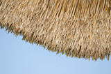 retro organic straw house roof blue sky background