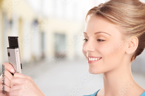 woman taking picture with phone in city