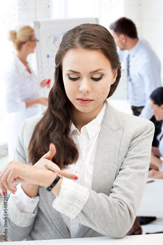 businesswoman looking at alarm clock