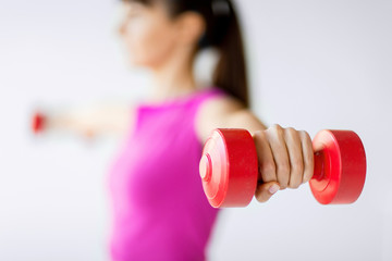 sporty woman hands with light red dumbbells