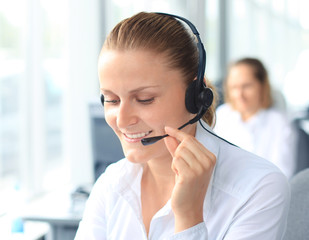young female call center operator with headset in office