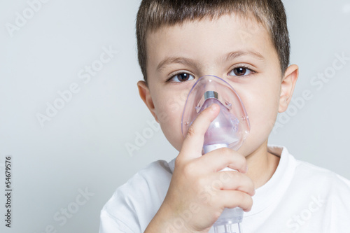Little boy having inhalation for easing cough