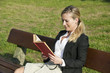 young woman reading a book on parn bench
