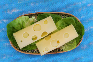 Slices of Swiss cheese on lettuce leaves