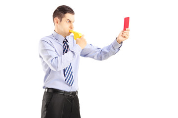 Young man blowing a whistle and showing a red card