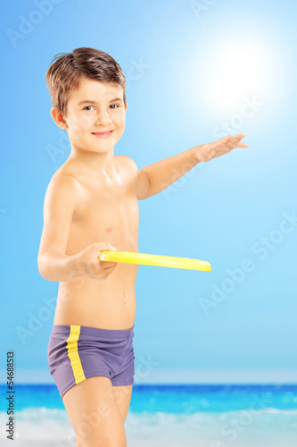 Smiling kid in shorts throwing frisbee on a beach