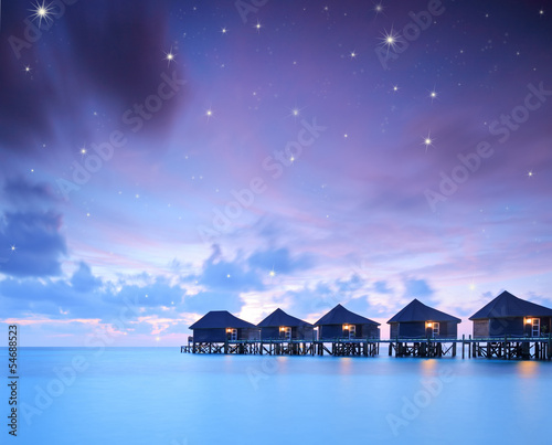 Starry skies over water villa cottages on island of Kuredu