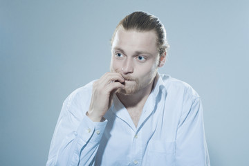 anxious man chewing on fingernails