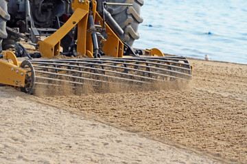 Sand Grader raking and lifting sand on public beach