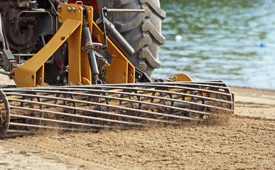 Sand Grader lifting and raking through sand on Public beach