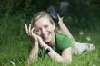 Junge blonde lachende Frau im Gras liegend