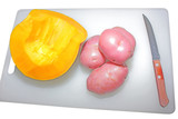 Pumpkin and potato on chopping board with knife isolated