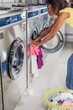 Woman Loading Washing Machine With clothes