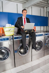 Businessman With Laptop In Laundry
