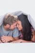 Couple under quilt hand in hand