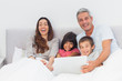 Happy family lying in bed using their laptop